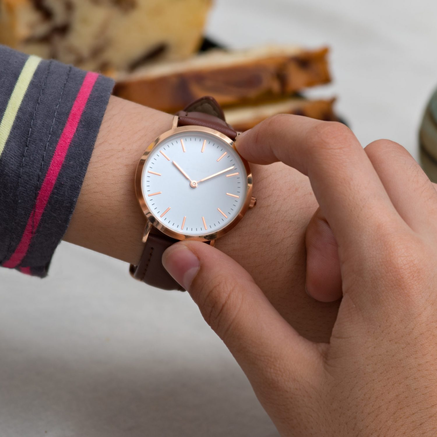 Classic wrist watch on girl's hand in front of hot chocolate and cake