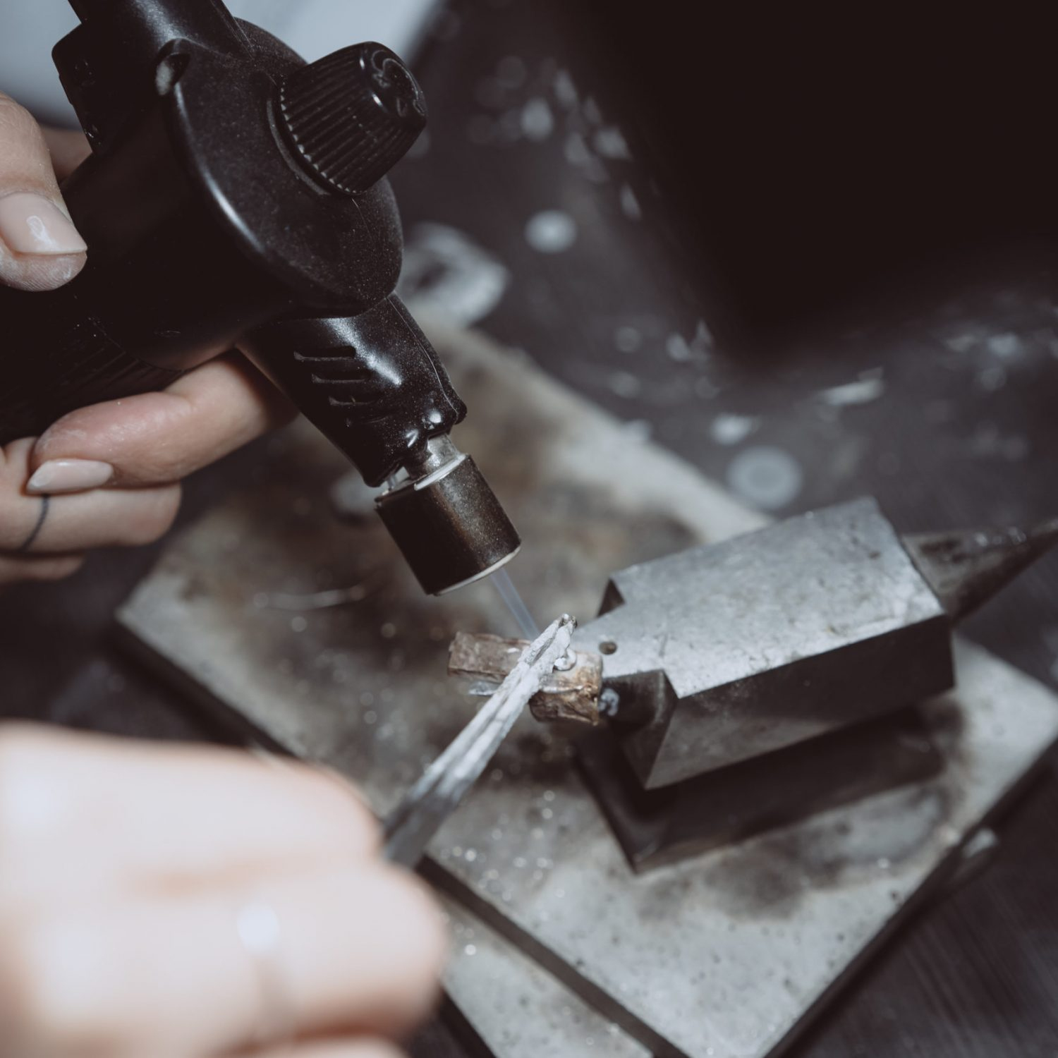 In the workshop, a woman jeweler is busy soldering jewelry on a workbench