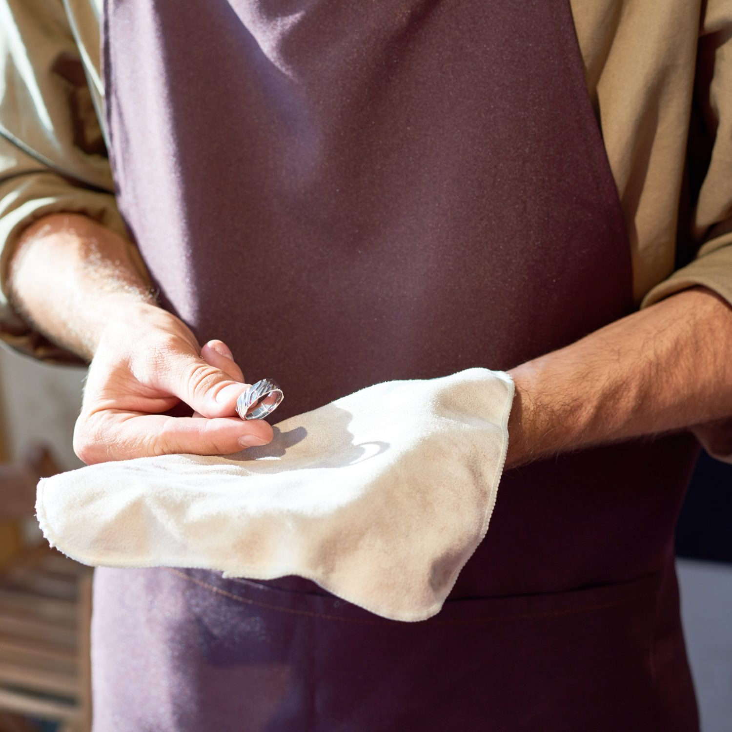 Mid section portrait of unrecognizable jeweler presenting newly made precious ring on cloth in his hands