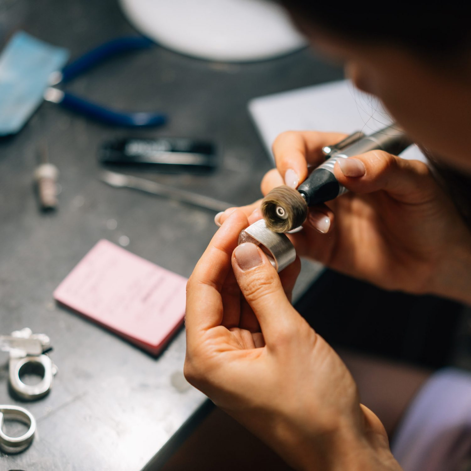 The girl works on a jewelry in the workshop. Jewelry repair shop. Tools, unfinished silverware and rough stones. The girl is a master jeweler.